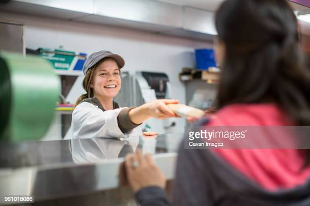 smiling worker giving packet to customer at supermarket - cavan images foto e immagini stock