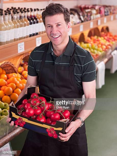 Souriant Travailleur tenant des tomates dans une épicerie