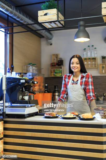 smiling worker in fast food restaurant - fast food restaurant stock pictures, royalty-free photos & images