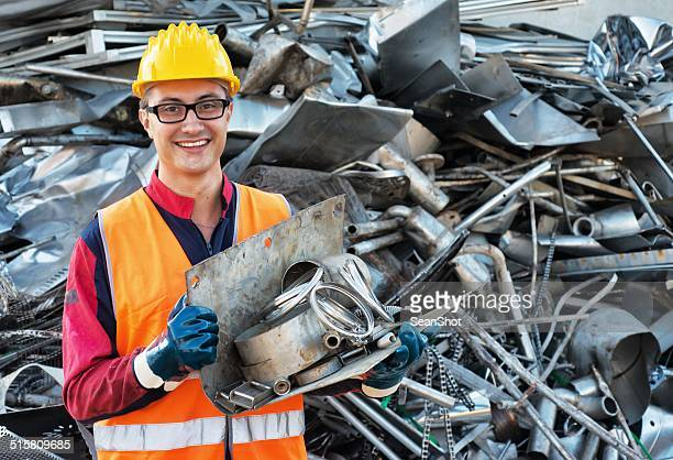 smiling worker in metal landfill - junkyard stock photos and pictures