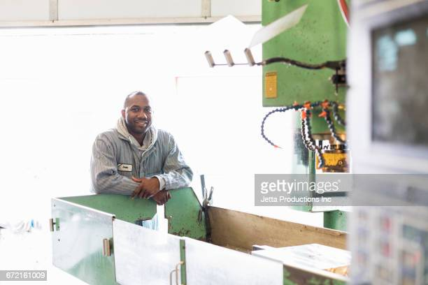 smiling worker leaning on machinery in factory - zakelijke kleding stock pictures, royalty-free photos & images