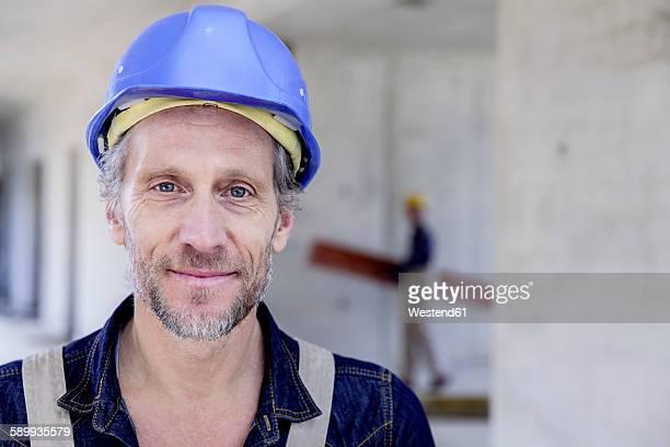 smiling worker on construction site - bauarbeiter stock-fotos und bilder