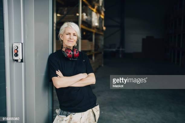smiling worker standing with arms crossed at entrance of industry - maschinenteil hergestellter gegenstand stock-fotos und bilder