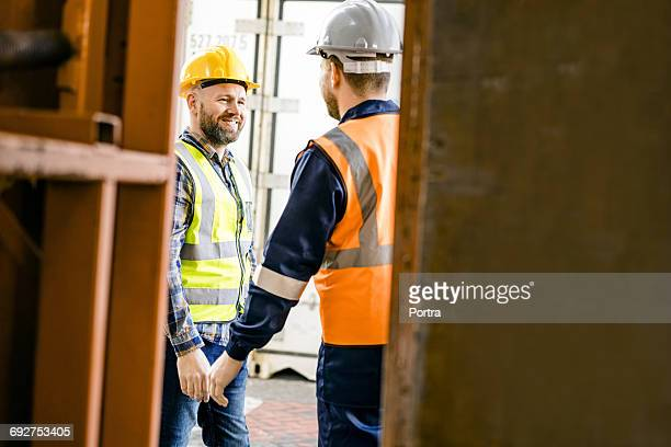Smiling worker talking with colleague at dock