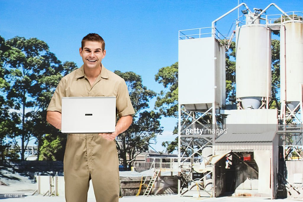 Smiling worker working on laptop in cement factory : Stock Photo