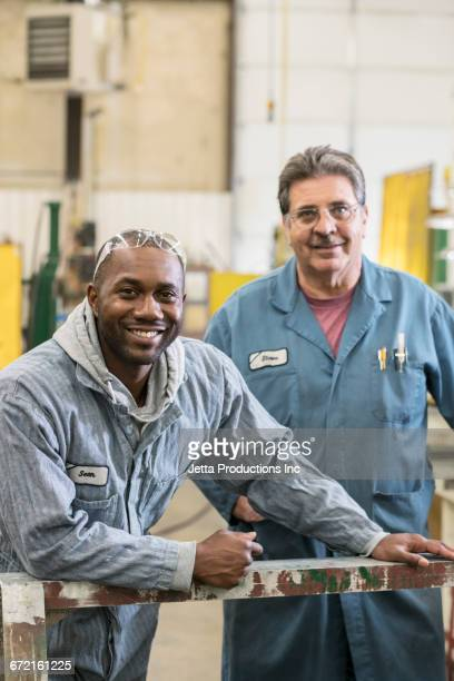 Smiling workers posing in factory
