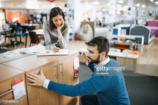 smiling workers taking measurements of a piece of furniture while working at the store. - furniture stock pictures, royalty-free photos & images