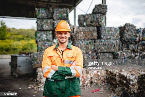 smiling workman outdoors at waste management facility - waste management stock pictures, royalty-free photos & images