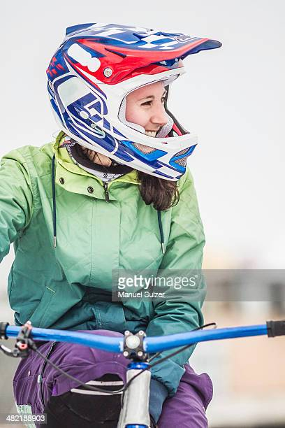 Smiling young adult female mountain biker on bike