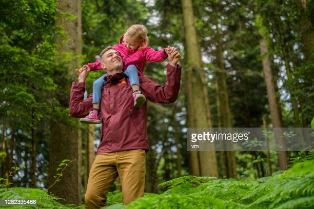 smiling young adult man carrying little girl on shoulders. - reality fernsehen stock pictures, royalty-free photos & images