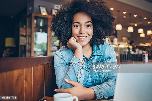 smiling young african ethnicity woman sitting in restaurant - creole ethnicity stock pictures, royalty-free photos & images