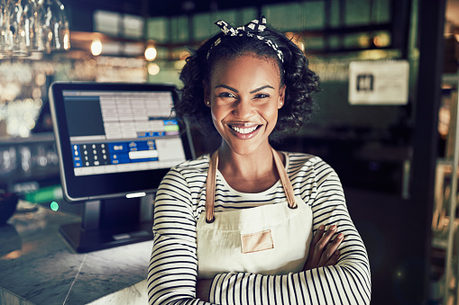 Smiling young African waitress behind the counter of a restaurant 946156854