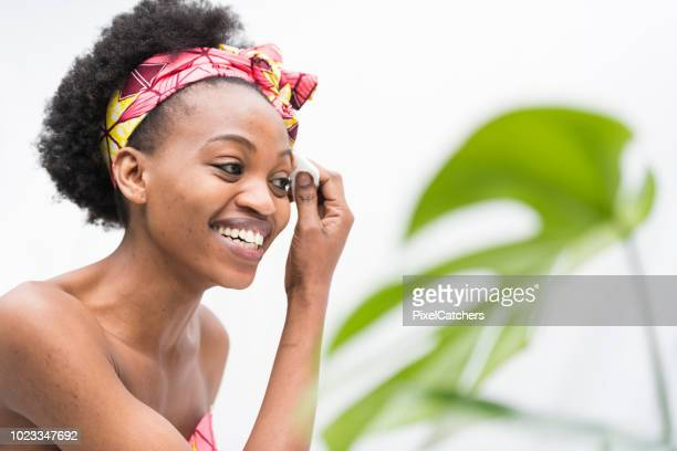 Smiling young African woman removing make up with cotton swab