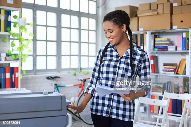 Smiling young african woman using copy machine in modern office
