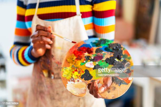 smiling young afro woman holding color palette and paintbrush - painter artist stock pictures, royalty-free photos & images