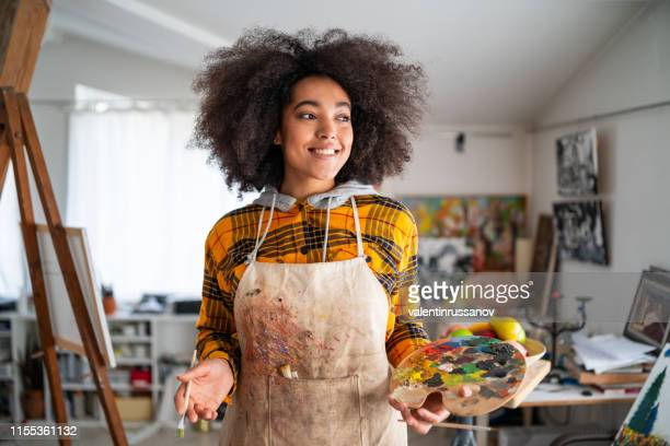 smiling young afro woman holding color palette and paintbrush - artist stock pictures, royalty-free photos & images