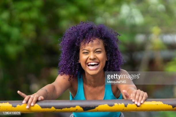 smiling young afro woman outdoors - purple hair stock pictures, royalty-free photos & images