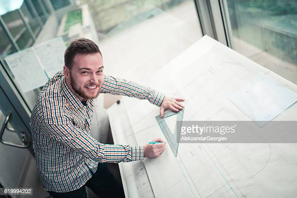 Smiling Young Architect Designer Working Blueprint Plans in His Office