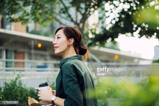 smiling young asian businesswoman using smartphone while having a healthy salad lunch box with a cup of coffee outdoors in an urban park during lunch break - city stock pictures, royalty-free photos & images
