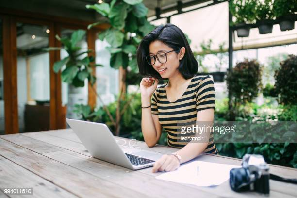 smiling young asian freelancer woman finishing up with work - authors stock pictures, royalty-free photos & images