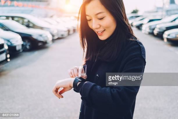 Smiling young Asian girl checking her smart watch in city street