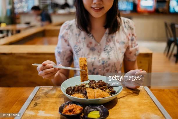 jeune femme asiatique de sourire mangeant des nouilles coréennes de sauce de haricot noir - tonkatsu photos et images de collection