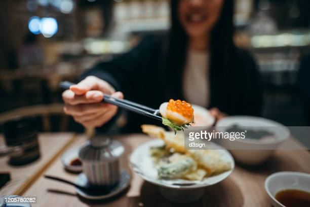 smiling young asian woman enjoying delicate japanese cuisine and seafood tempura in a japanese restaurant - travel ストックフォトと画像