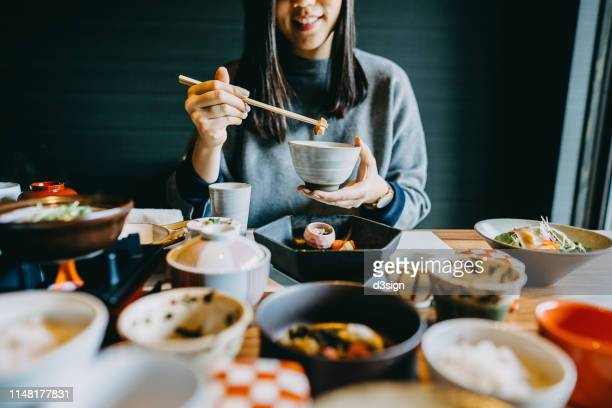 smiling young asian woman enjoying delicate japanese style cuisine with various side dishes, seafood and green tea in restaurant - washoku fotografías e imágenes de stock