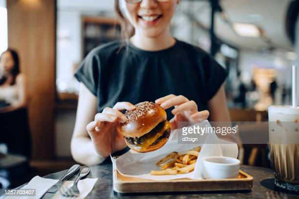 smiling young asian woman enjoying freshly made delicious burger with fries and a glass of iced coffee in a cafe - ファーストフード ストックフォトと画像