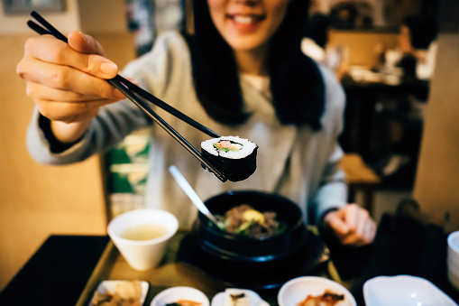 Smiling young Asian woman enjoying kim bap with chopsticks in a Korean restaurant - gettyimageskorea