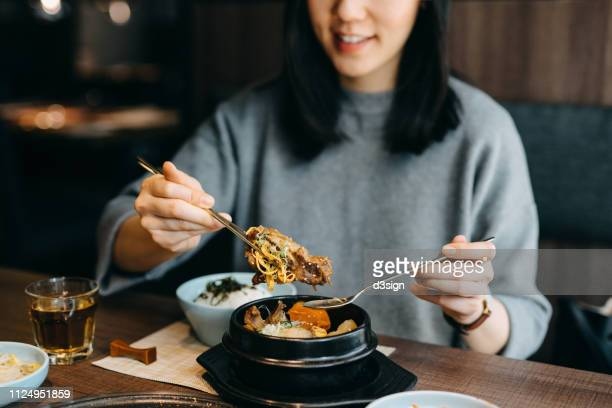smiling young asian woman enjoying korean meal in a korean restaurant - キムチ ストックフォトと画像