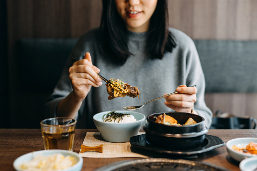 Smiling young Asian woman enjoying traditional Korean cuisine in a Korean restaurant - gettyimageskorea