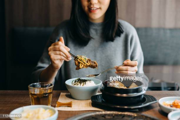 smiling young asian woman enjoying traditional korean cuisine in a korean restaurant - asian food stock pictures, royalty-free photos & images