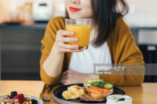 smiling young asian woman holding a glass of juice while having breakfast at home - beginnings stock pictures, royalty-free photos & images