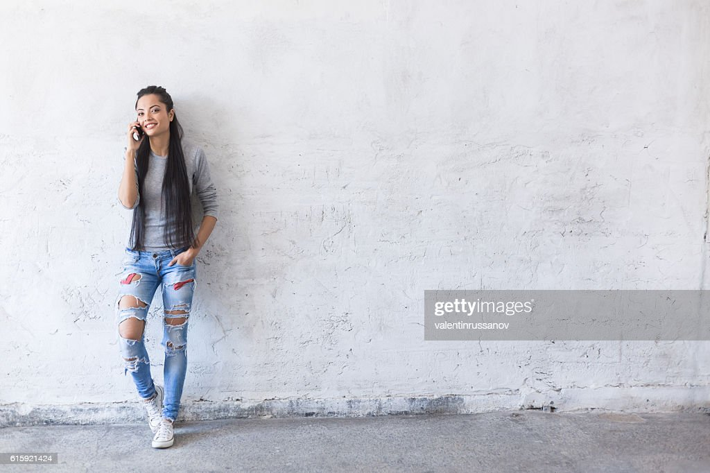 Smiling young asian woman leaning back on blank wall : Stock Photo
