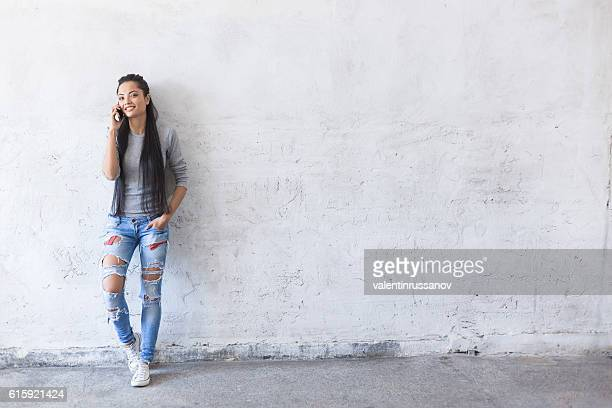Smiling young asian woman leaning back on blank wall