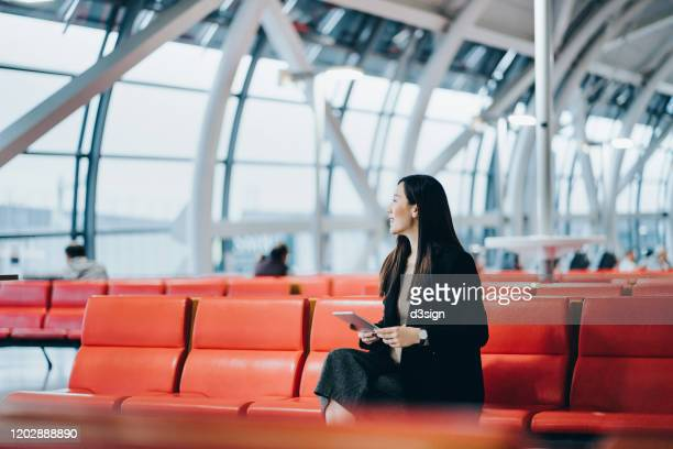 smiling young asian woman reading on digital tablet while waiting for her flight in airport lounge - geschäftsreise stock-fotos und bilder