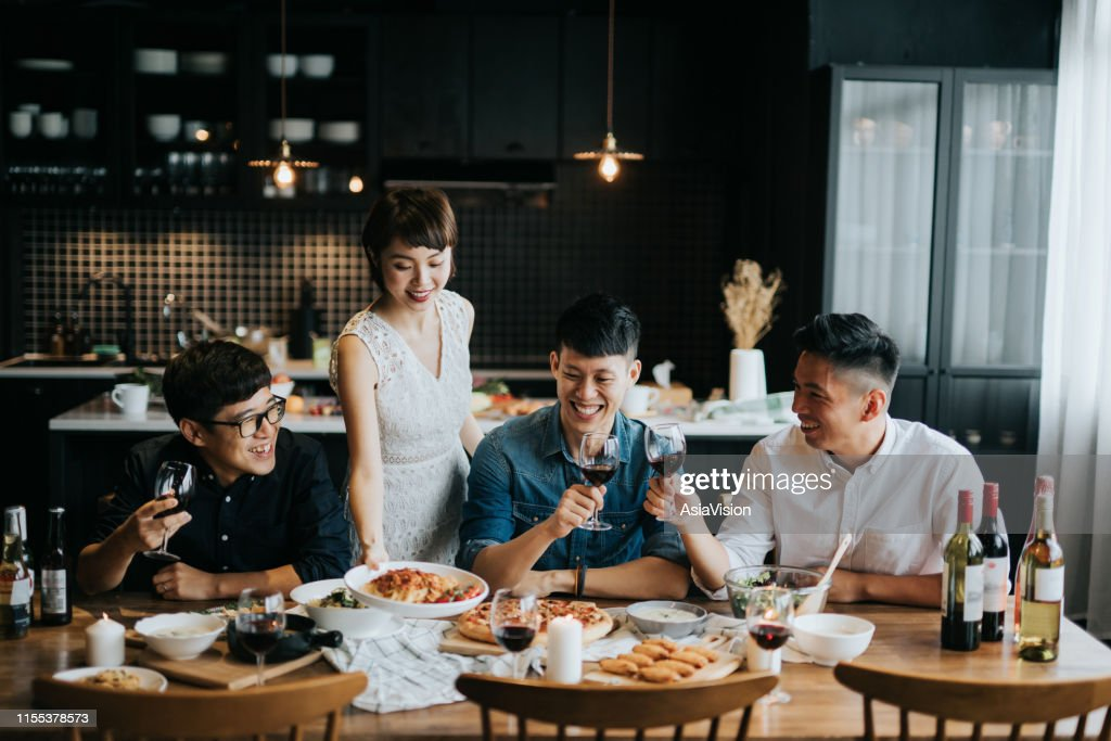 Smiling young Asian woman serving food to friends during party at home, they are smiling joyfully and toasting with red wine : Stock Photo