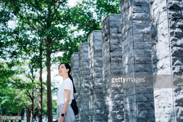 smiling young asian woman taking a break, enjoying the freshness of the nature in a urban park in the city - holy city park stock pictures, royalty-free photos & images