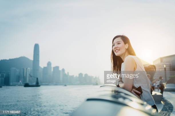 smiling young asian woman traveller looking out over promenade of victoria harbour enjoying the gentle breeze and the beautiful cityscape at dusk - image stock pictures, royalty-free photos & images
