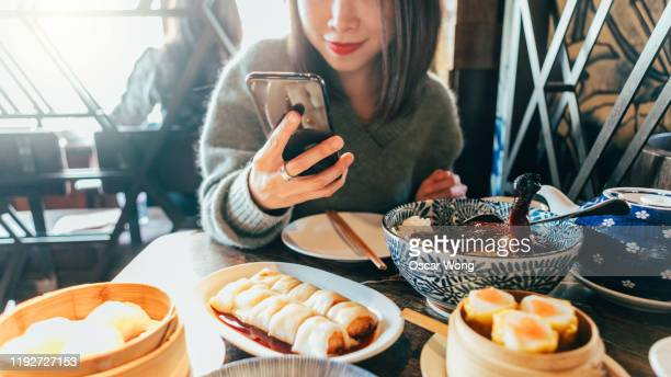 smiling young asian woman using smartphone while having dim sum in a chinese restaurant - ready to eat stock pictures, royalty-free photos & images