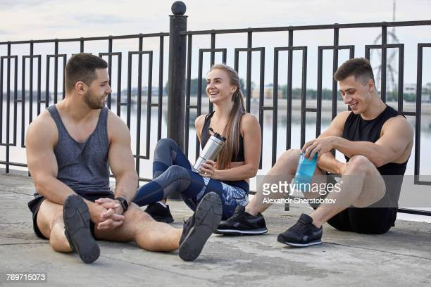 Smiling young athletes taking break while sitting on footpath by railing