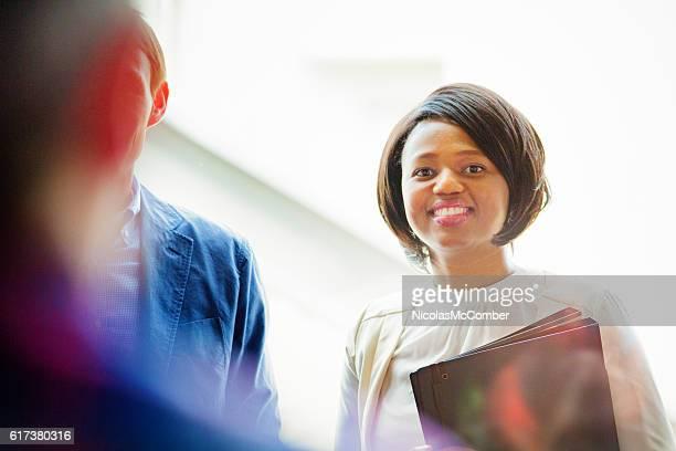 lächelnde junge schwarze büroangestellte bereit für die ausbildung - tag 1 stock-fotos und bilder