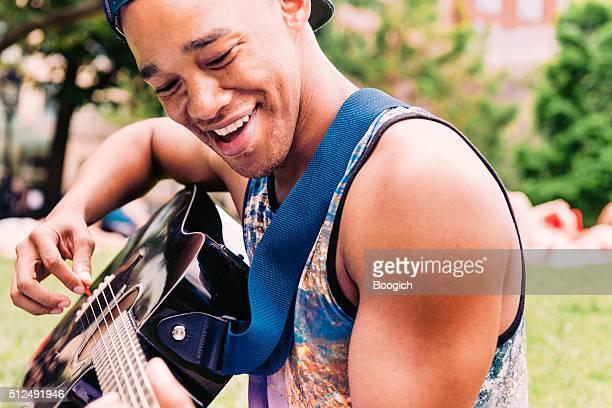 Lächelnd jungen schwarzen Mann spielen Akustikgitarre in NYC Park