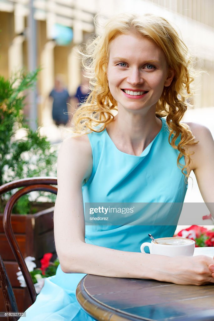 Smiling young blond woman in cafe with cup of cappuccino : Foto de stock
