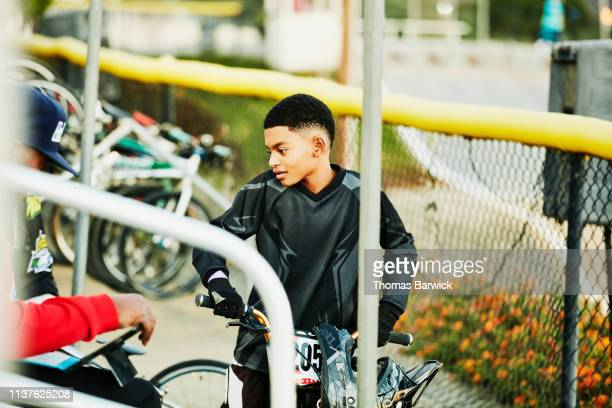 smiling young bmx racer talking with father in stands before race - 自転車競技 ストックフォトと画像