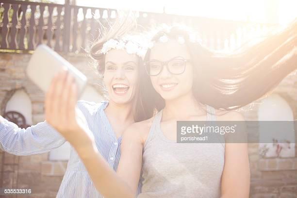 Smiling young boho women making selfie