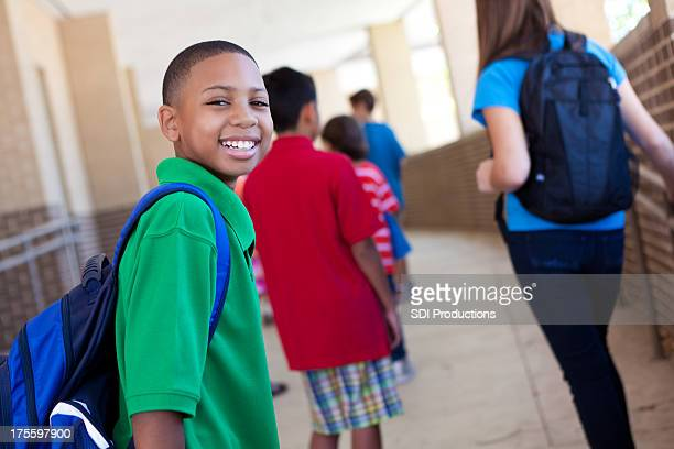 Smiling young boy at school with other students
