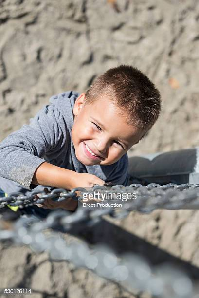 Smiling young boy climbing chain playground