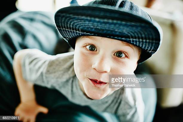 Smiling young boy leaning off chair in living room
